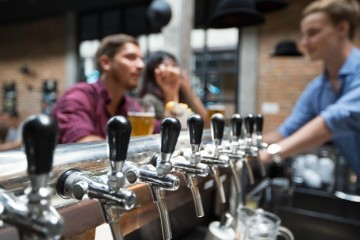 customers-bartender-and-beer-taps-in-pub_1262-3529